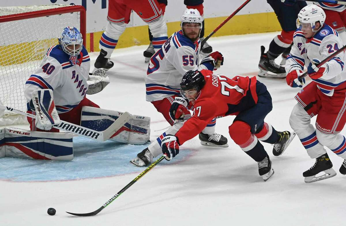 Capitals right wing T.J. Oshie (77) reaches for the puck in front of the Rangers goal during the game between Washington and New York on Wednesday, Oct. 13, 2021.