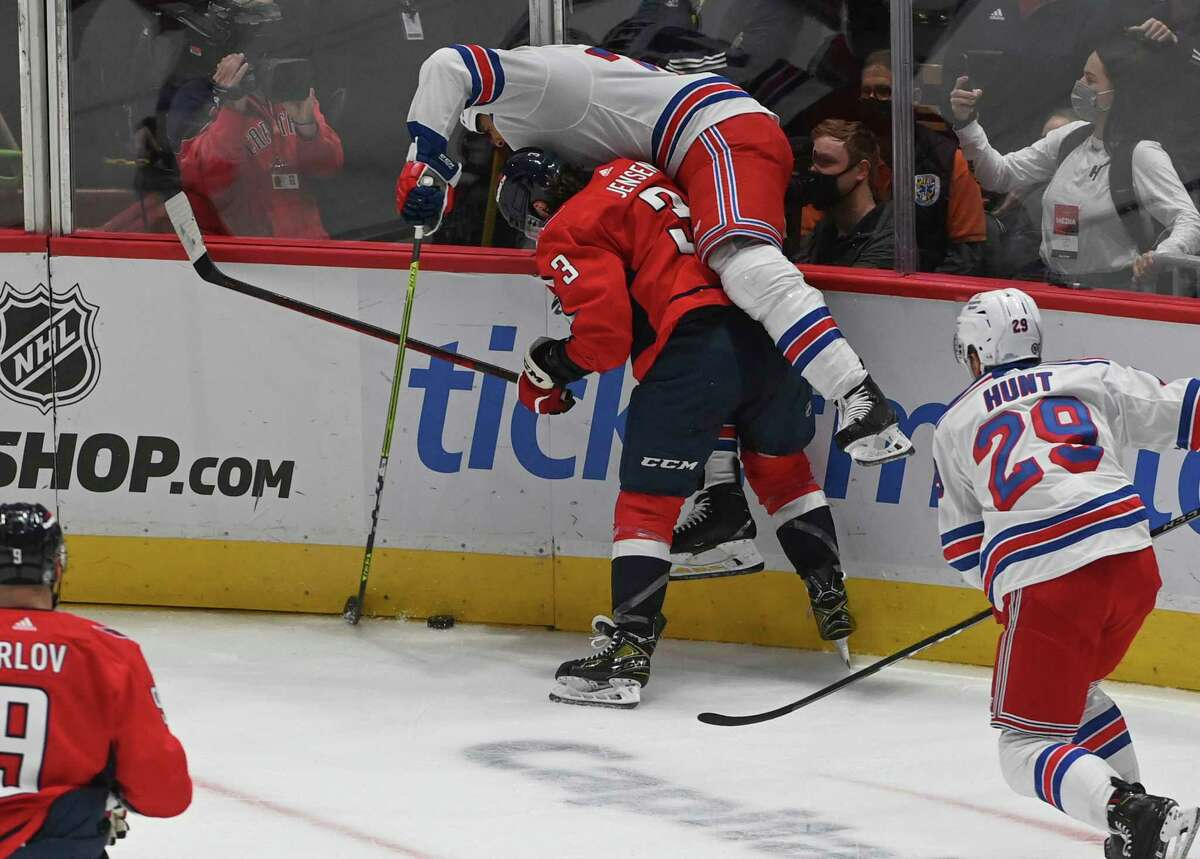 A Rangers player goes up over Capitals defenseman Nick Jensen along the boards during the game between New York and Washington on Wednesday, Oct. 13, 2021, at Capital One Arena in Washington, D.C.