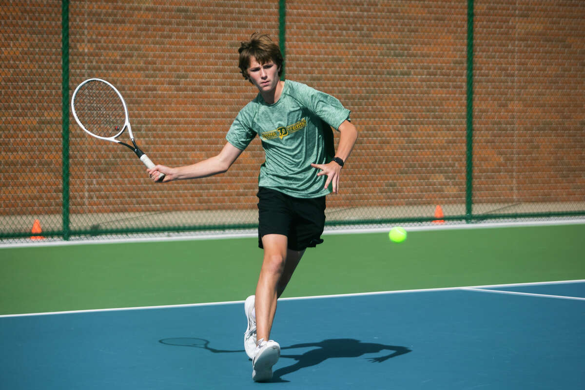 Dow High's Austin King prepares to return a shot during a Sept. 9, 2021 match against Midland High.