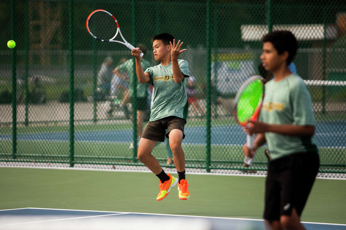 Dow High's Boaz Qiu hits a forehand during a Sept. 9, 2021 match against Midland High.