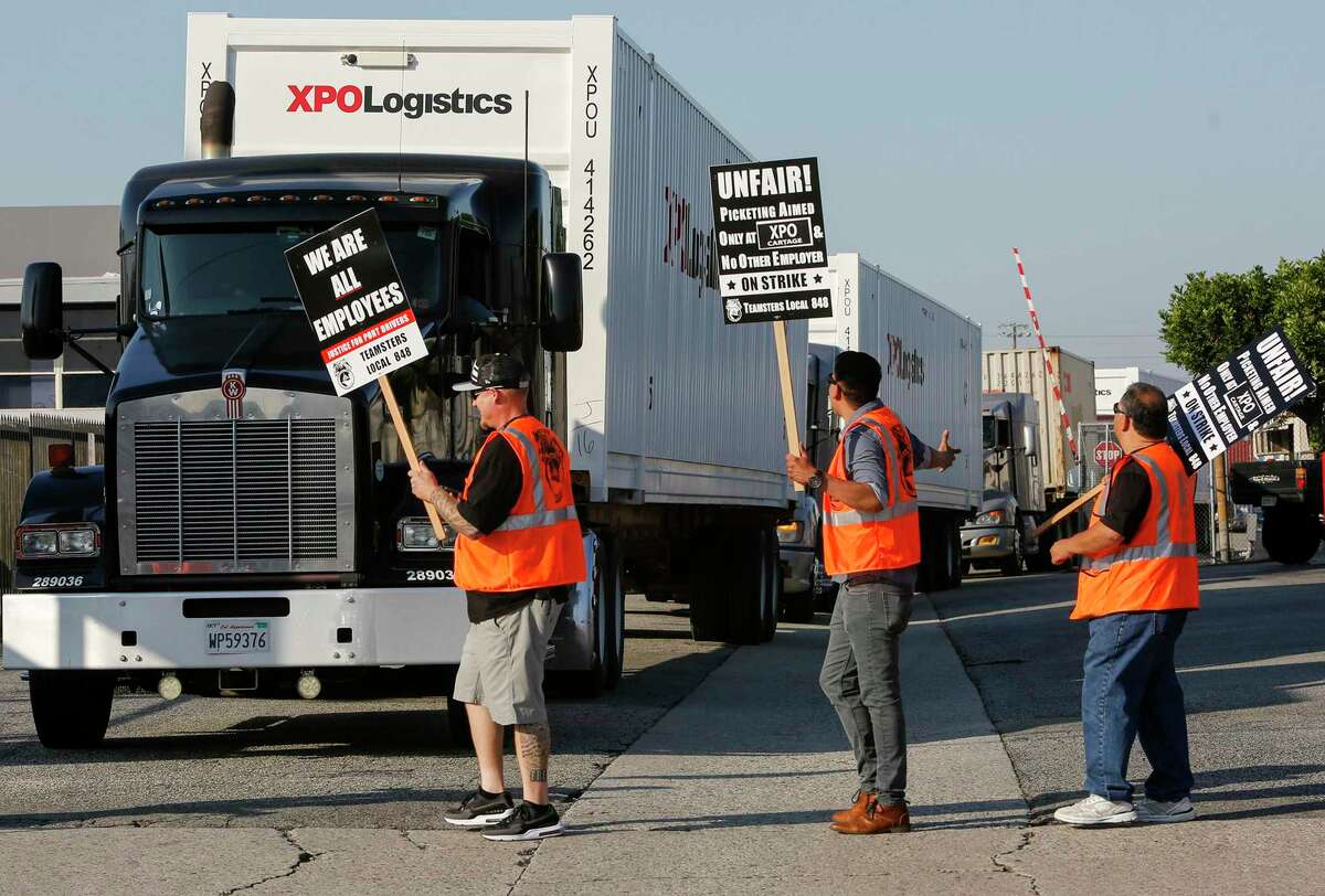 Port truck drivers picket at a XPO Logistics facility in Commerce, Calif., in 2017. A federal judge in California has given preliminary approval to two settlements of class-action lawsuits against XPO that would total nearly $30 million.