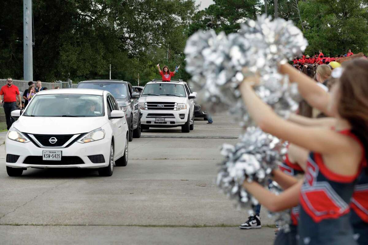 Cars drive the circuit of the parking lot by the various floats during this year's Oak Ridge High School Homecoming parade on the campus parking lot Wednesday, Oct. 13, 2021 in Conroe, TX. The theme of this year's parade is cartoon shows, with each class or organization dressed up as or displaying icons from their favorite shows.