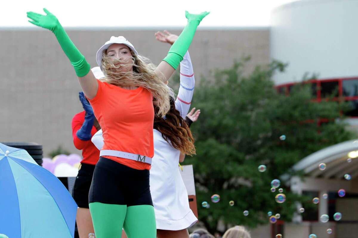 Student Cheer members, dressed in SpongeBob Squarepant attire, dance on their float as cars drive by during this year's Oak Ridge High School Homecoming parade on the campus parking lot Wednesday, Oct. 13, 2021 in Conroe, TX. The theme of this year's parade is cartoon shows, with each class or organization dressed up as or displaying icons from their favorite shows.