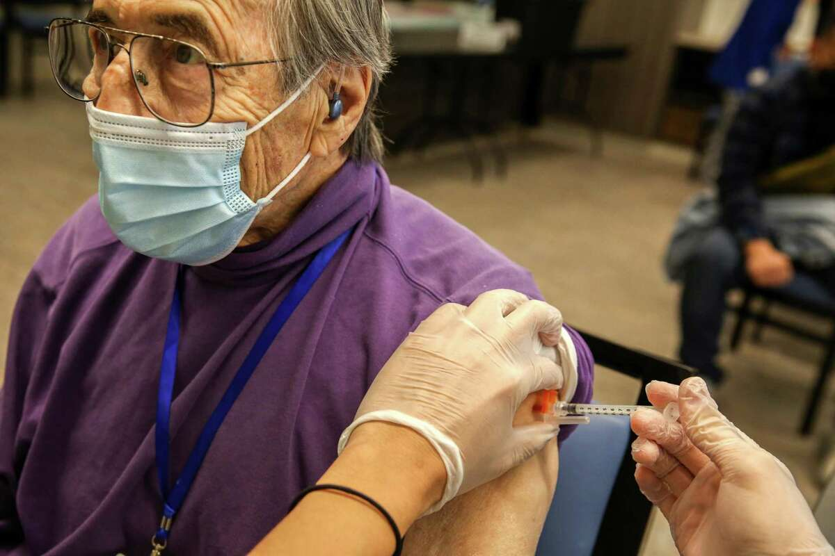 Morton Brown holds still while getting a COVID-19 booster shot at a San Francisco assisted living facility.