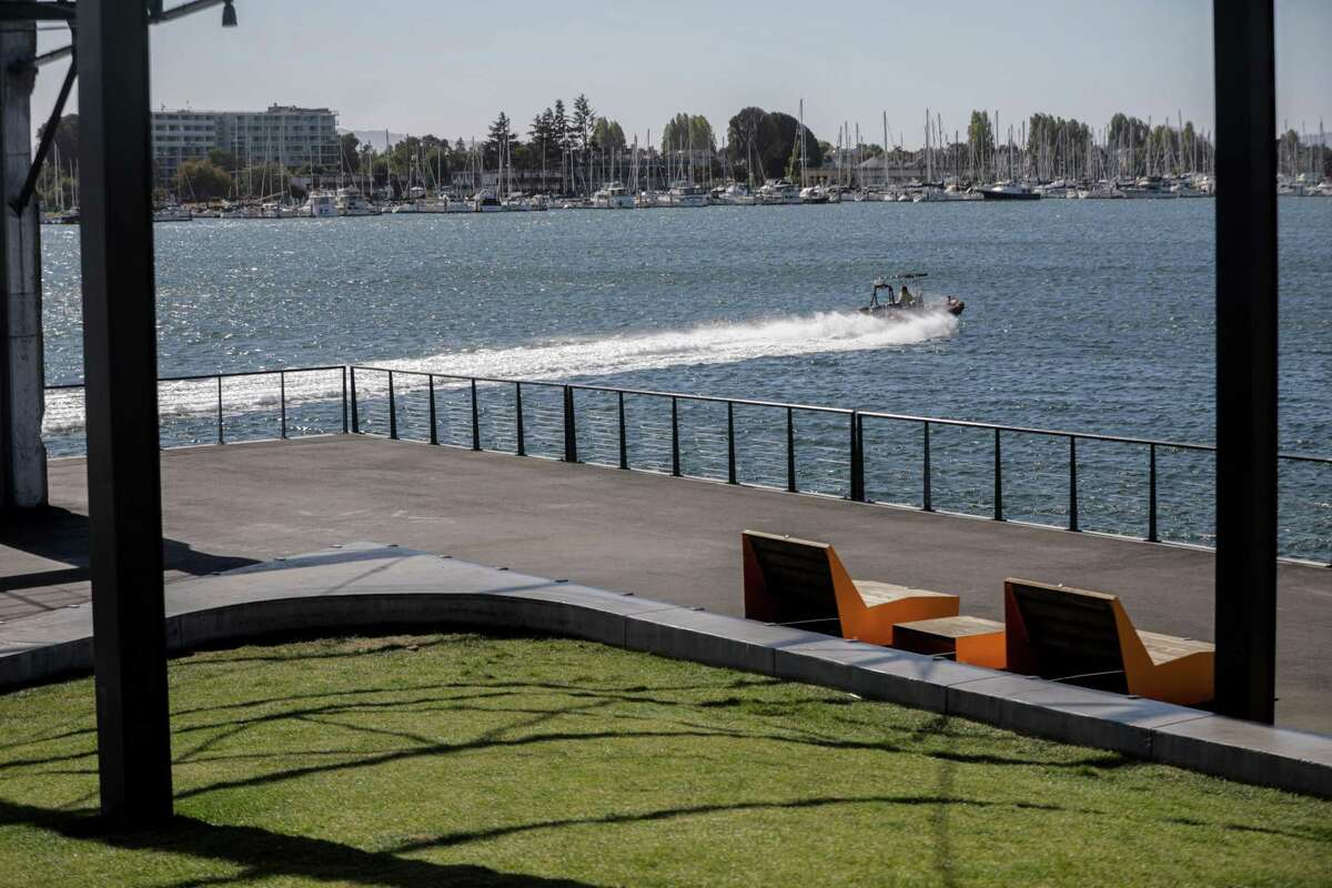 A boat speeds by Township Commons in Oakland, Calif. on Monday, Oct. 11, 2021. There is a new proposal to add a marina that would have slips lining the entire public space.