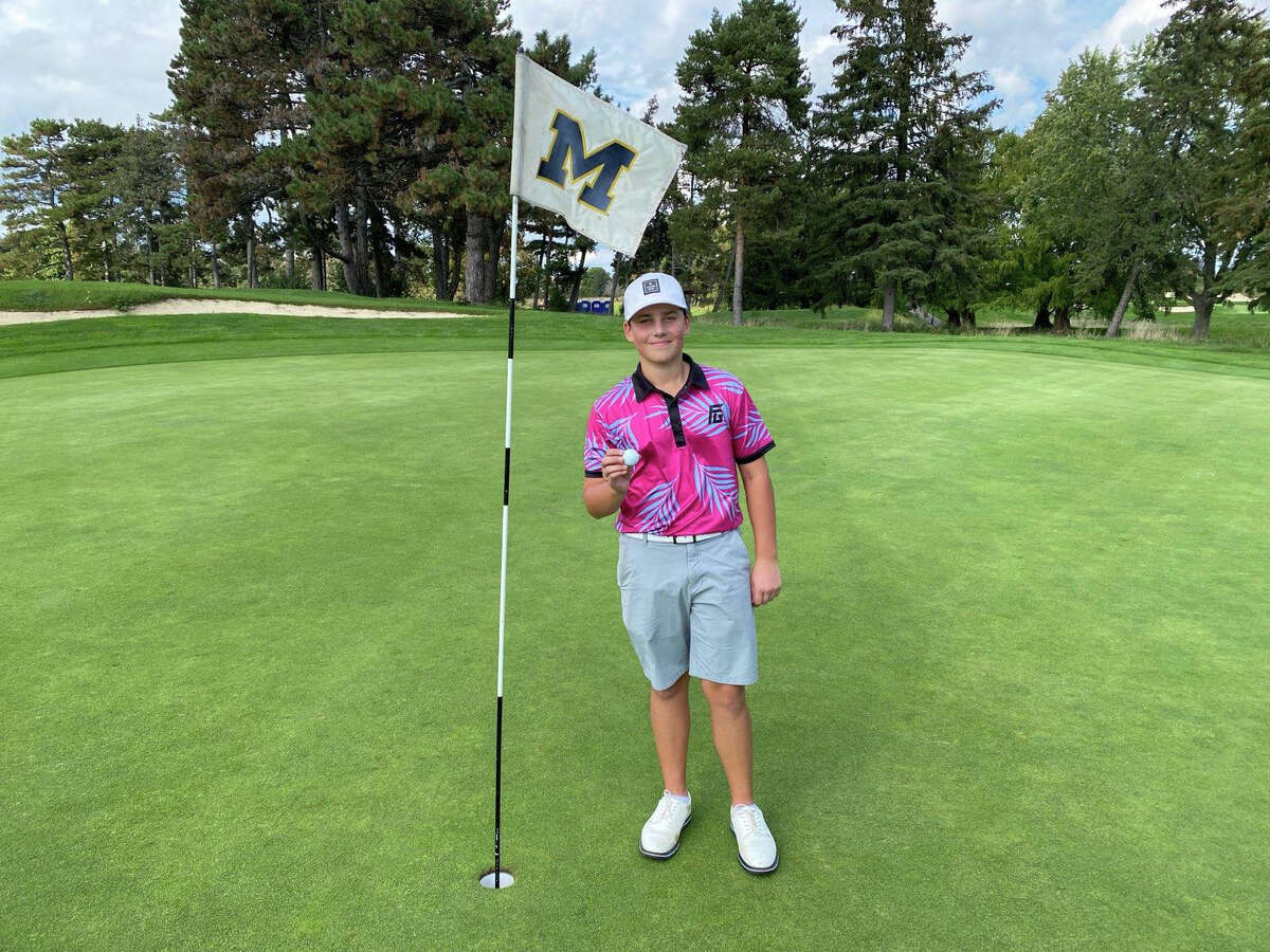 Dow High sophomore Carson Everett, 15, holds the ball he used to shoot a hole-in-one on the 220-yard 12th hole at the University of Michigan Golf Course recently.