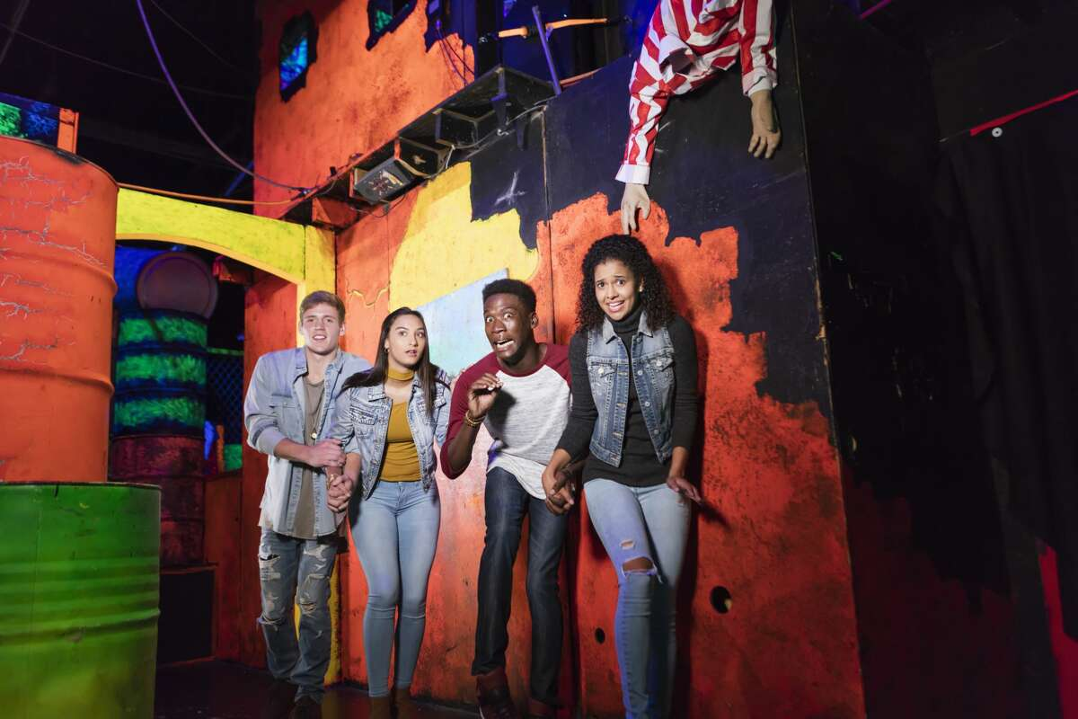 Pictured is a group of four young adults having fun in a halloween haunted house.