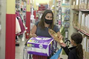 Lilia De Rosa, of Danbury, and her daughter Isabella, age 7, wear masks as they shop Ocean State Job Lot in Danbury, Conn, on Tuesday, September 28, 2021. Danbury's mask mandate is lifted as of 12:01 a.m. Friday.