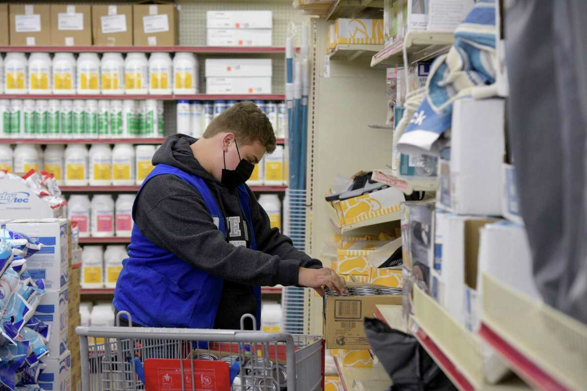 Jacob Maciulewicz, of Ridgefield, a sales associate at Ocean State Job Lot in Danbury, Conn, wears a mask as he stocks a shelf on Tuesday, September 28, 2021. Danbury's mask mandate is lifted as of 12:01 a.m. Friday.
