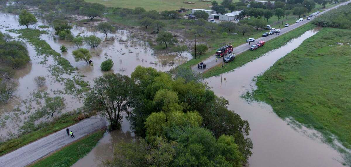 Officials search a flooded creek Thursday, Oct. 14, 2021, after floodwaters from overnight rains swept away several cars and left two people missing in the St. Hedwig area.