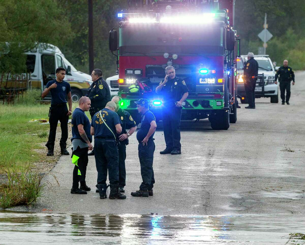 Officials work Thursday, Oct. 14, 2021, near St. Hedwig after floodwaters from overnight rains swept away several cars and left two people missing.