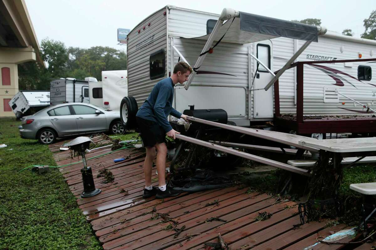 Austin McGhee, 17, helps clean up by his family's recreational vehicle at the River Ranch RV Resort in New Braunfels, Texas, Thursday, Oct. 14, 2021. Heavy rains from Tropical Storm Pamela flooded Guadalupe River overnight. One RV was swept away by the high waters and several others were damaged. Some places in the area received over 5 and a half inches of rain according to CoCoRaHS.