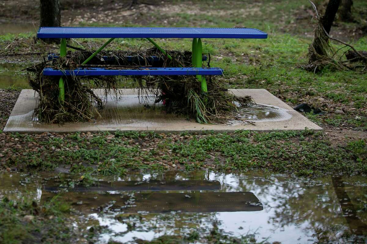 A picnic table covered with debris is reflected in a large puddle following heavy rainfall at Raymond Rimkus Park in Leon Valley, Texas, on Oct. 14, 2021.