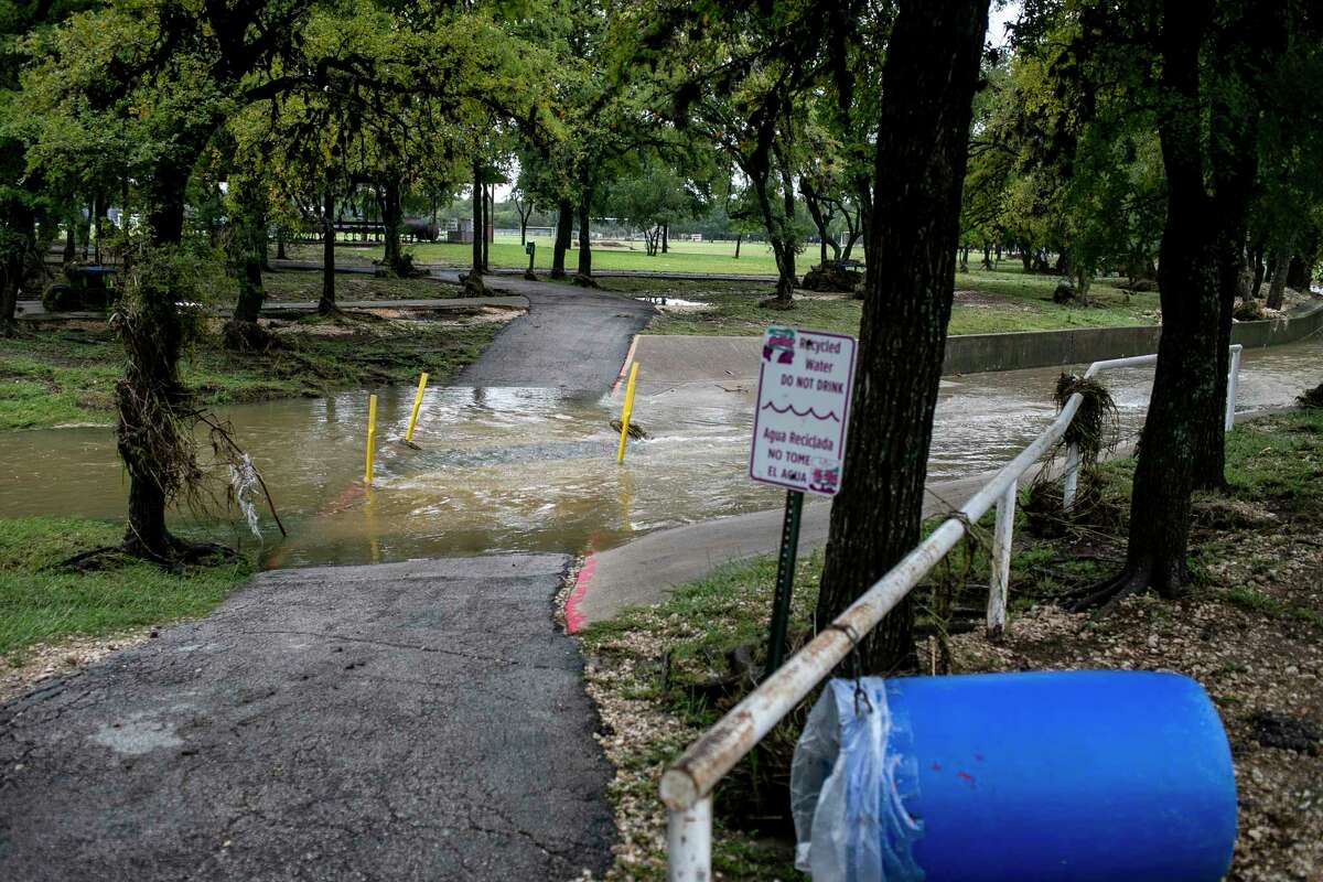 A swollen creek flows over a pedestrian path after heavy rainfall at Raymond Rimkus Park in Leon Valley, Texas, on Oct. 14, 2021.
