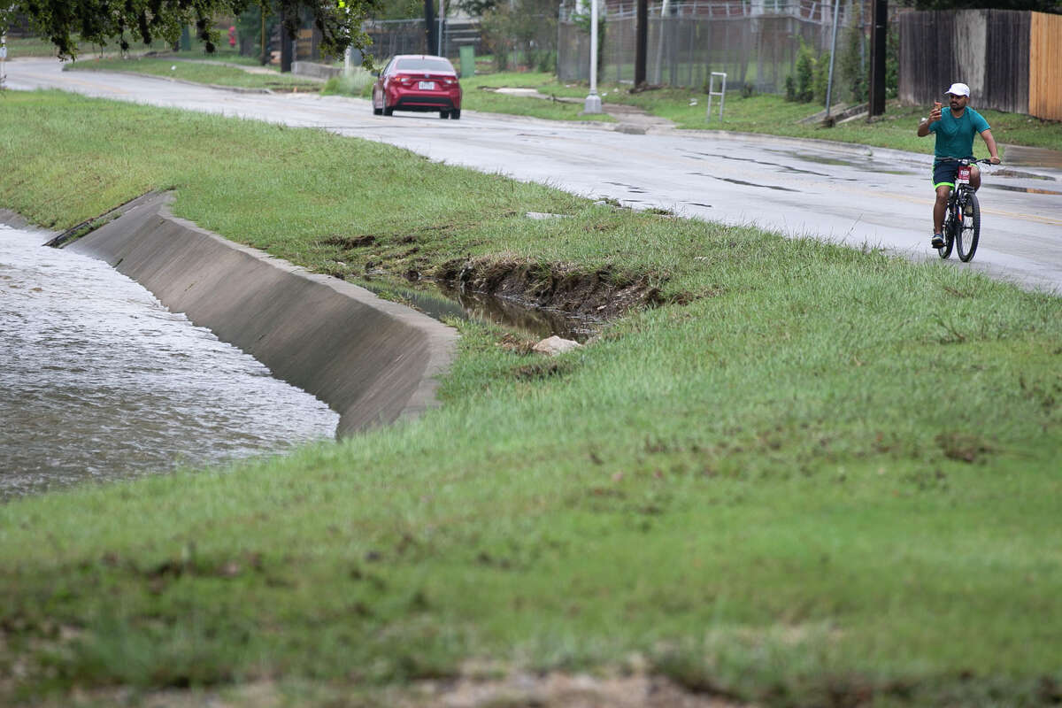 While riding his bike, Aseem Jain of Leon Valley takes in the view of the swollen creek that runs along Raymond Rimkus Park in Leon Valley, Texas, on Oct. 14, 2021.