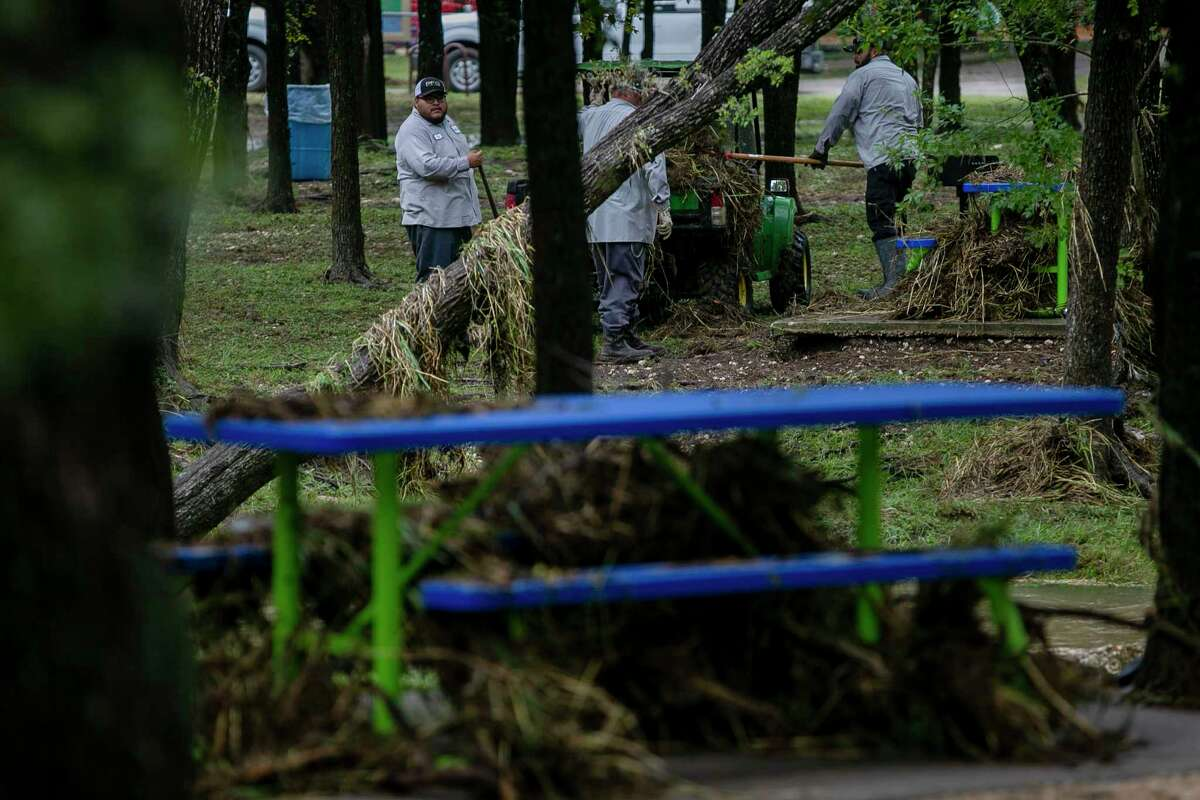 Crews clean up debris following flooding at Raymond Rimkus Park in Leon Valley, Texas, on Oct. 14, 2021.