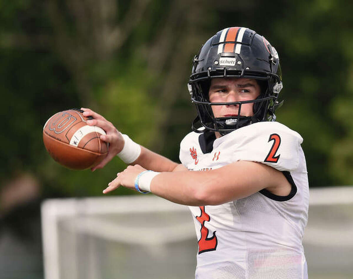Edwardsville quarterback Jake Curry warms up on the sideline prior to the start of Saturday's game against Belleville East in Belleville.