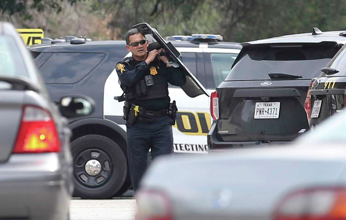 A San Antonio police officer shields himself during a standoff at Seven Oaks Apartments at 5903 Danny Kaye in the Medical Center area on Wednesday, Oct. 13, 2021. The man whom police were facing was later found dead with an apparently self-inflicted gunshot wound, police said.