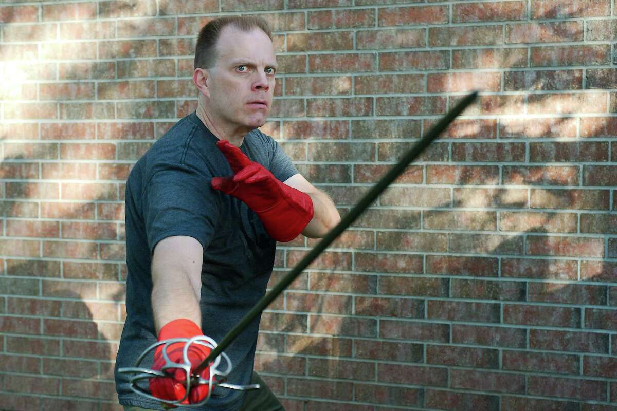 """League City resident H. Russ Brown demonstrates a sword-fighting technique that will be used in his farce """"A Divine Kerfuffle,"""" which he is directing at COM Theatre in Texas City. Brown is the college's head of theater and the artistic director of COM Theatre."""