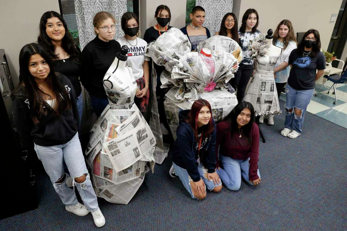 Students (on floor from left) Trinity Velazquez and Anahi Gomez, with (behind, from left) Yulitza Hernandez, Mayra Mejia, Nikitta Thomas, Dayna Hiland, Angelica Palacios, David Rivera Ortiz, Diana Rubio, Stefanie Martinez, Hailey Bolen, and Angie Castro with their original dress designs made from newspapers at Caney Creek High School Thursday, Oct. 14, 2021 in Conroe, TX.