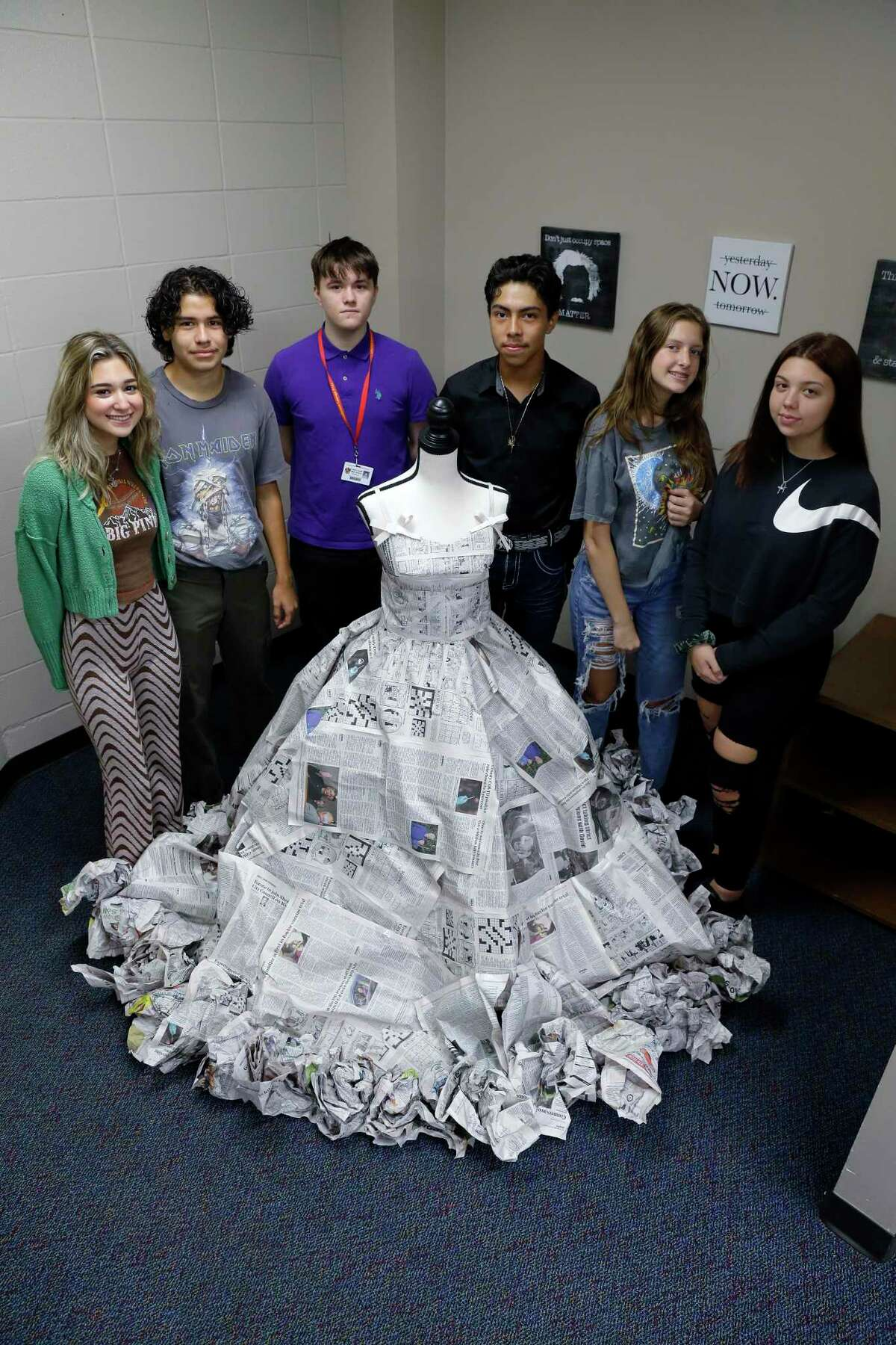Students, from left, Reese Manchaca, Jessy Villa, Caden Brown, Jose Bolanos, Kaylee Duncan, and Jasmine Van Veckhoven with their original dress designs made from newspapers at Caney Creek High School Thursday, Oct. 14, 2021 in Conroe, TX.