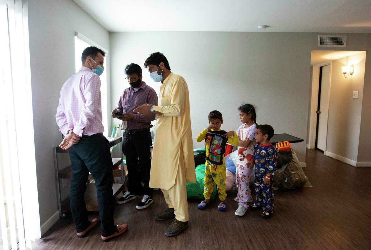 Zabihullah Hamidi, from left, and Nar Baraili, case workers of Interfaith Ministries for Greater Houston, shows Afghan parolee Atiqullah, 37, how to use gift cards as his children, Irfanullah, 6, Iqra, 7, and Mohammad Yamar, 5, watch in their new two-bedroom apartment, provided by Interfaith Ministries for Greater Houston, Sept. 13, 2021, in Southwest Houston.