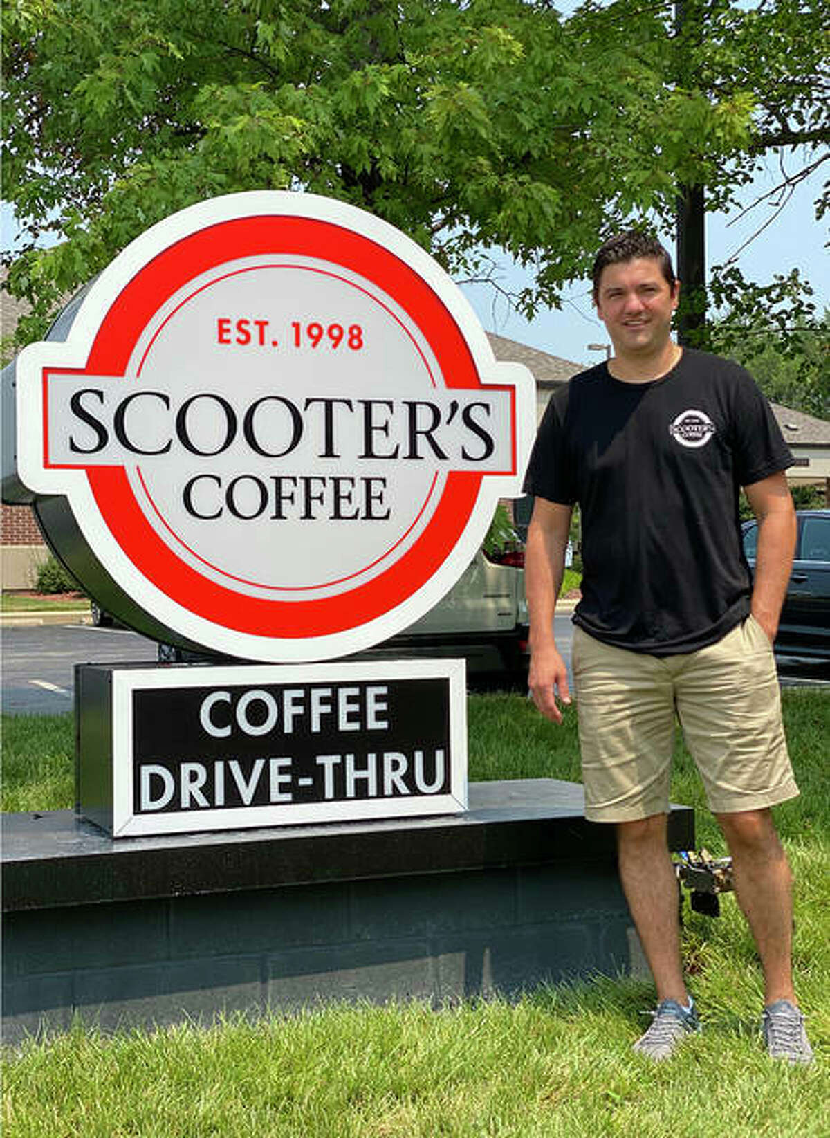 Robert Semptimphelter, owner of the Glen Carbon Scooter's Coffee that opened in August, is shown next to a sign for the business. Plans have been announced for a Godfrey Scooter's Coffee; village officials are waiting to review a formal proposal for the drive-through coffee shop.
