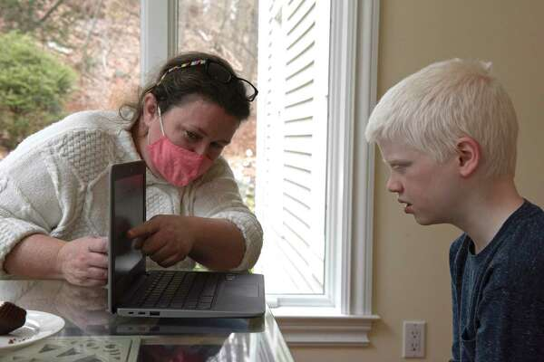 Helen Quinn works with her son James at their home on Wednesday, January 13, 2021, in Danbury, Conn. Danbury schools saved money last academic year on transportation, tutors and substitute teachers due to remote learning. Technology costs rose, however.