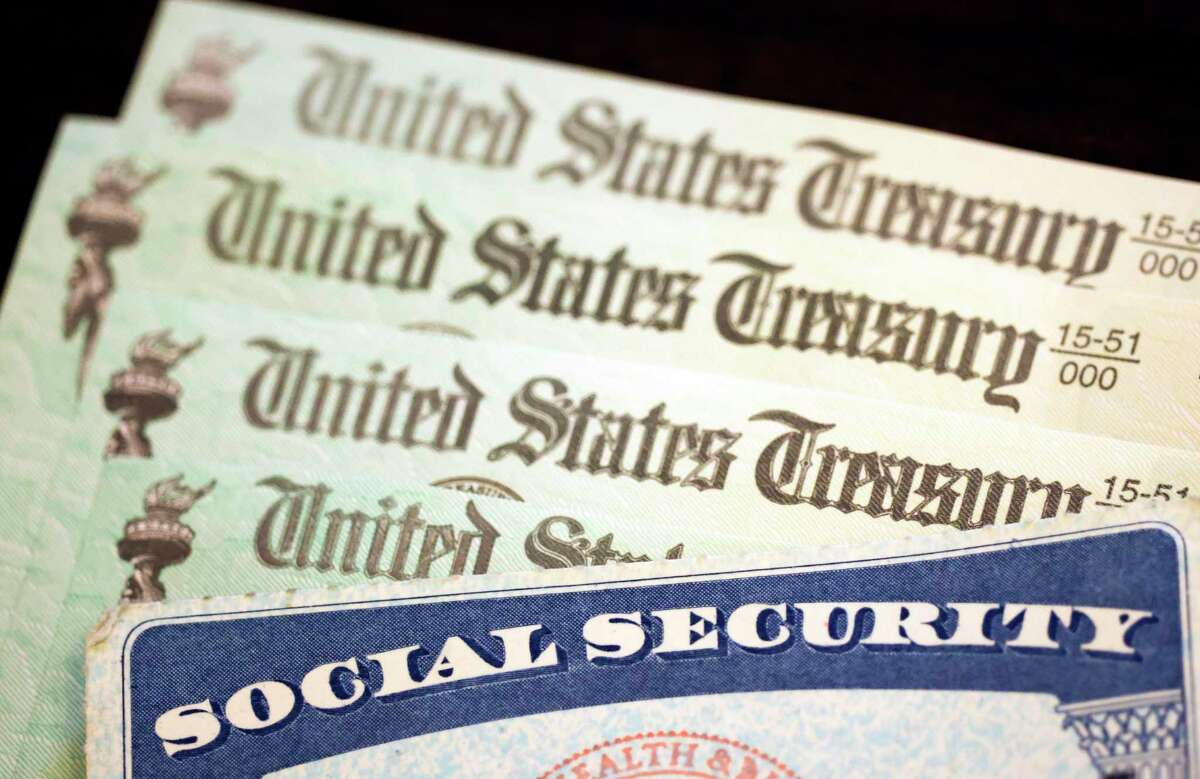 In this photo illustration, a Social Security card sits alongside checks from the U.S. Treasury on October 14, 2021.