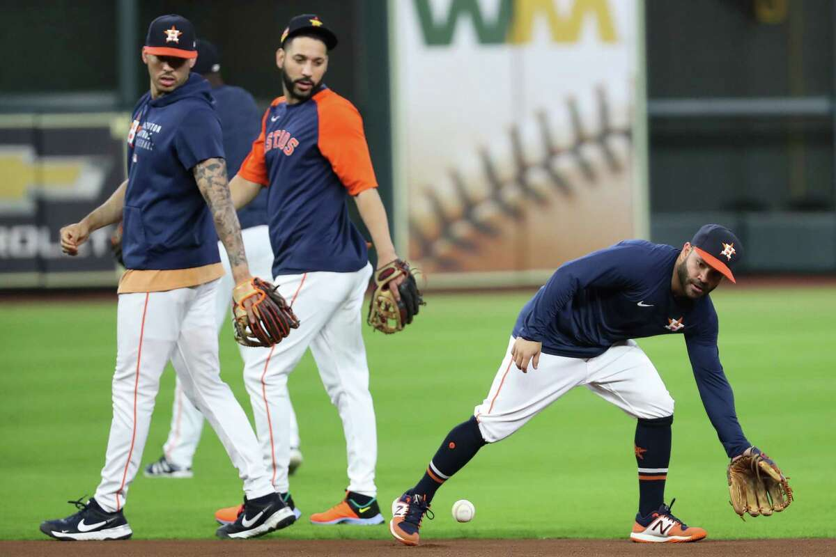 Houston Astros second baseman Jose Altuve, right, reaches down to pick, up a grounder as teammates Carlos Correa and Marwin Gonzalez walk past during a workout before Game 1 of the American League Championship Series against the Boston Red Sox Thursday, Oct. 14, 2021 in Houston.