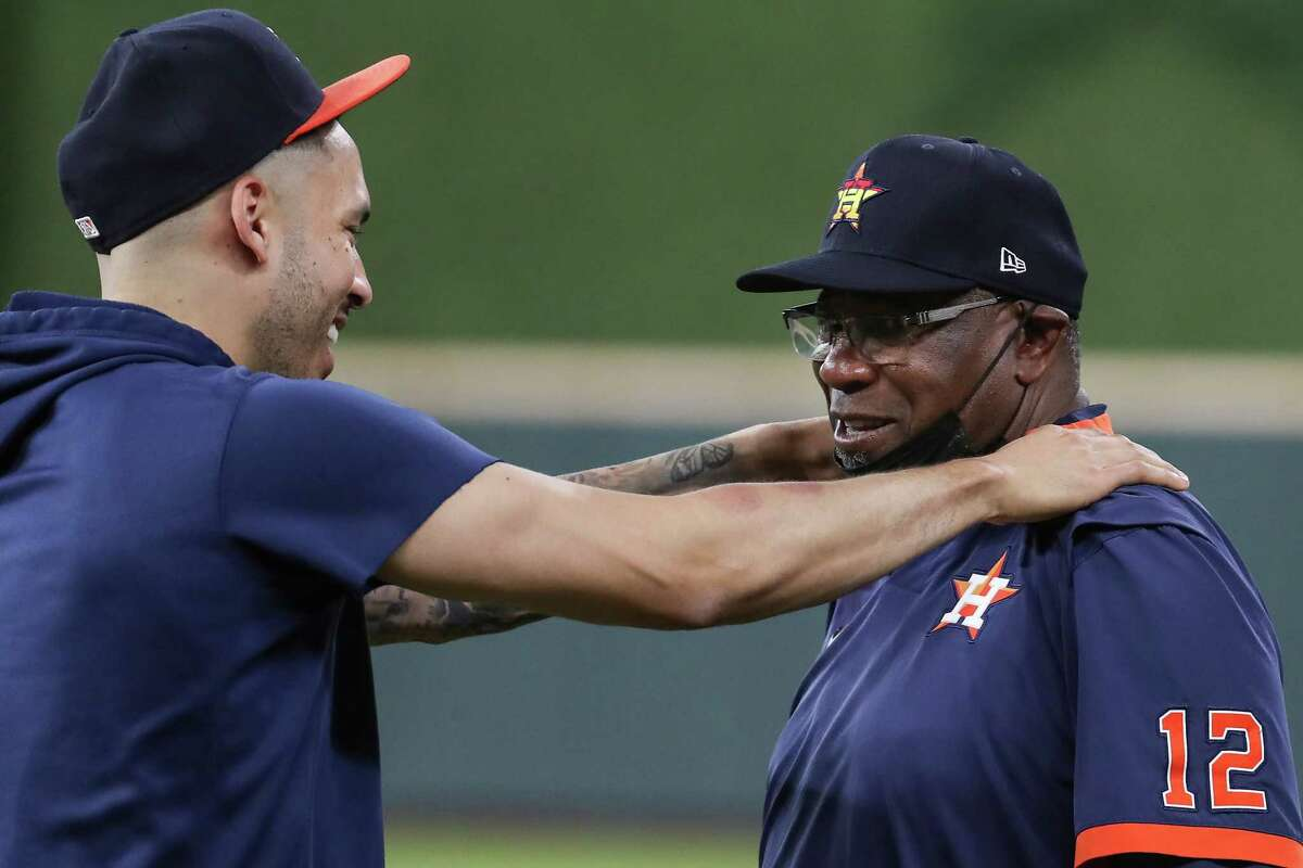 Houston Astros shortstop Carlos Correa, left, and manager Dusty Baker Jr. interact on the field during a workout the day before Game 1 of the American League Championship Series against the Boston Red Sox Thursday, Oct. 14, 2021 in Houston.