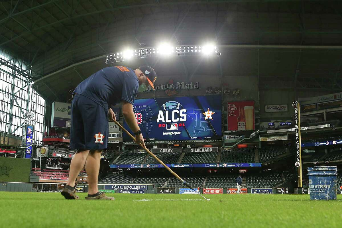 Mike Idecker, of the Houston Astros grounds crew, paints the third base coaches box the day before a workout before Game 1 of the American League Championship Series between the Astros and the Boston Red Sox Thursday, Oct. 14, 2021 in Houston.