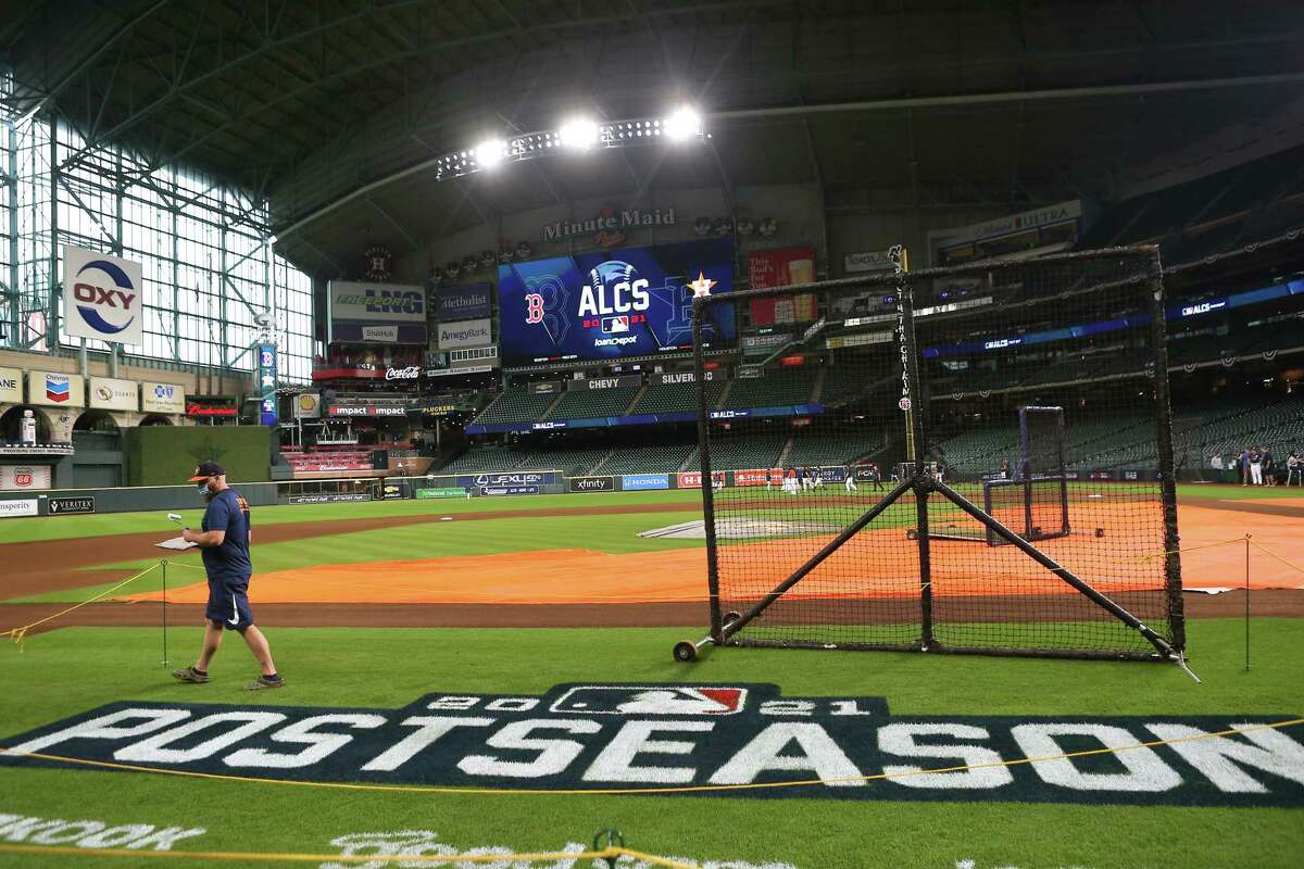 Mike Idecker, of the Houston Astros grounds crew, touches up the post season logo on the field before a workout the day before Game 1 of the American League Championship Series between the Astros and the Boston Red Sox Thursday, Oct. 14, 2021 in Houston.
