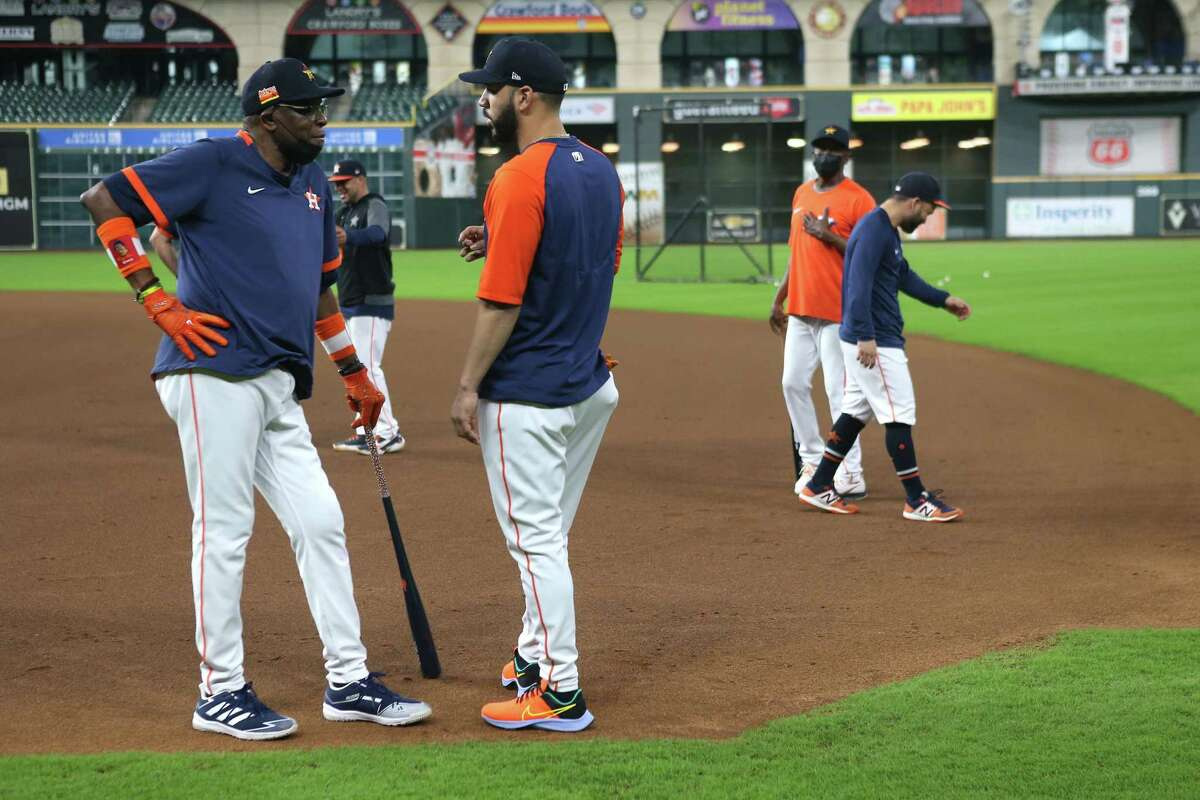 Houston Astros manager Dusty Baker Jr., let, talks to Marwin Gonzalez on the field during a workout before Game 1 of the American League Championship Series against the Boston Red Sox Thursday, Oct. 14, 2021 in Houston.