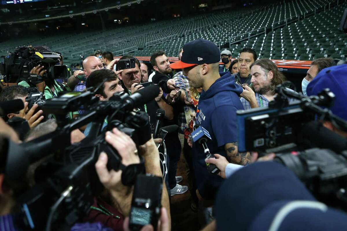 Houston Astros shortstop Carlos Correa is surrounded by media as he comes of the field during a workout before Game 1 of the American League Championship Series against the Boston Red Sox Thursday, Oct. 14, 2021 in Houston.