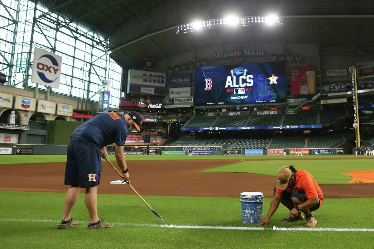 Mike Idecker, left and Sixto Zapata, of the Houston Astros grounds crew, paint the third base coaches box before a workout the day before Game 1 of the American League Championship Series between the Astros and the Boston Red Sox Thursday, Oct. 14, 2021 in Houston.