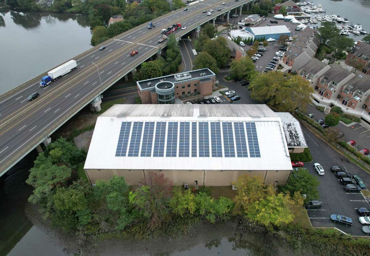 Solar panels are installed on the roof of the Greenwich Racquet Club in the Cos Cob section of Greenwich, Conn. Wednesday, Oct. 13, 2021. The Board of Selectmen's Energy Management Committee has a goal of reducing the town's energy consumption and costs by 20 to 40 percent through initiatives like LED bulbs and installation of solar panels through renewable energy credits.