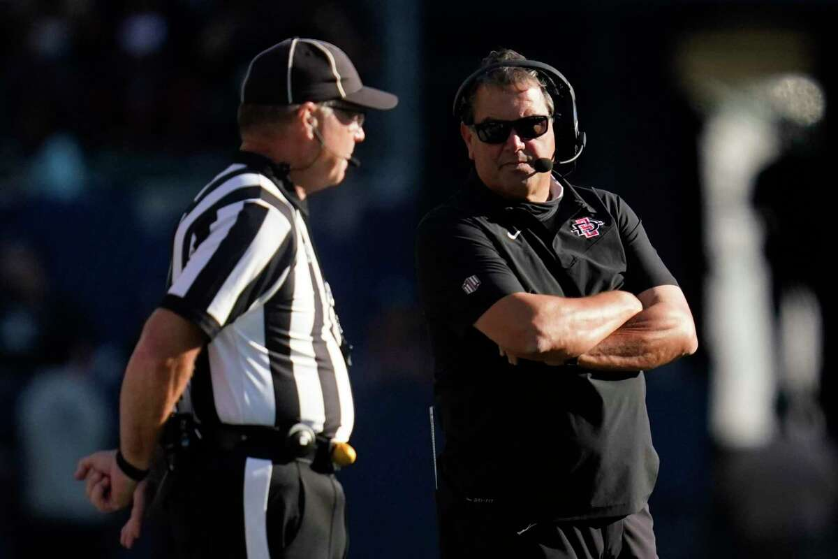 San Diego State head coach Brady Hoke, right, talks with an official during the first half of an NCAA college football game against Utah Saturday, Sept. 18, 2021, in Carson, Calif. (AP Photo/Ashley Landis)