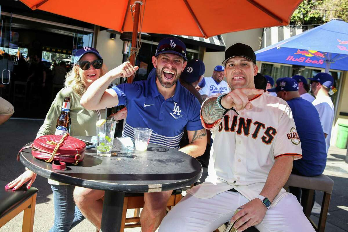 From left, Dodgers fans Brittney Houk, Zach Stensrud and Giants fan Jimmy Souza cheer on their teams at Momo's in San Francisco on Thursday.