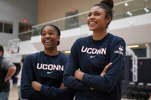 UConn's Aubrey Griffin, left, and Olivia Nelson-Ododa, right, watch the men's team shoot before the Huskies' men's and women's basketball teams' annual First Night celebration on Oct. 18, 2019, in Storrs, Conn. UConn's incoming freshmen will experience First Night, unlike last year's class, in front of students only.