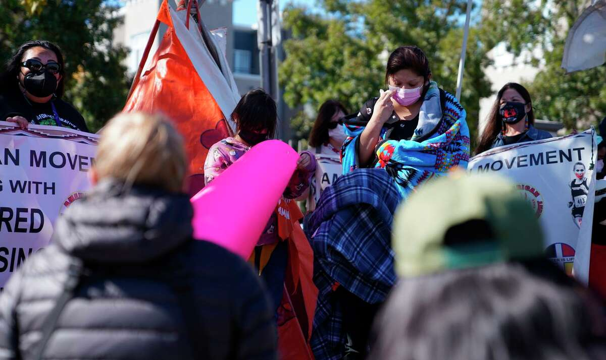Ruby Rodriguez (right, in a pink mask) speaks during a rally to recognize missing and slain Indigenous women in Oakland. Rodriguez's sister, Bessie Walker, was slain this year.