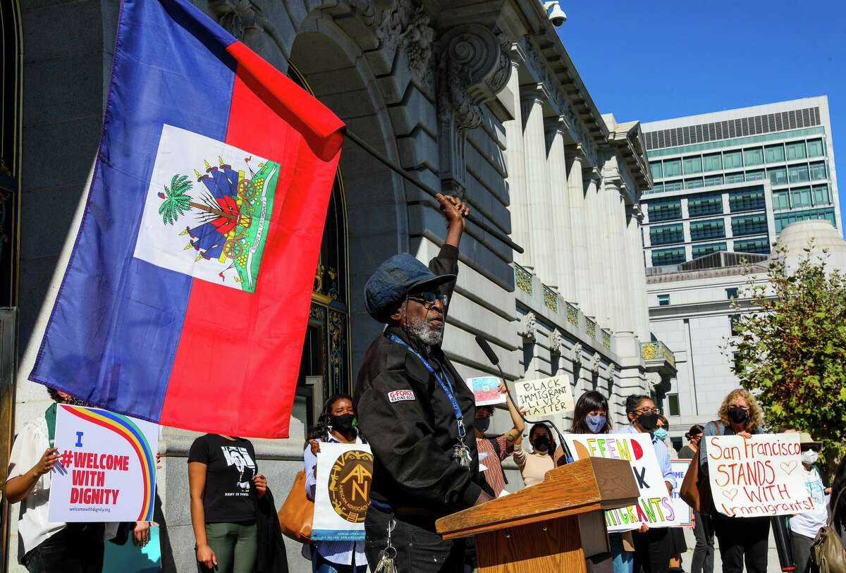 Ustadi Kadiri, with the Haiti Action Committee, holds an Haitian flag while criticizing the expulsion of Haitian asylum seekers from the U.S. during a rally in front of San Francisco City Hall on Thursday, Oct. 14, 2021.