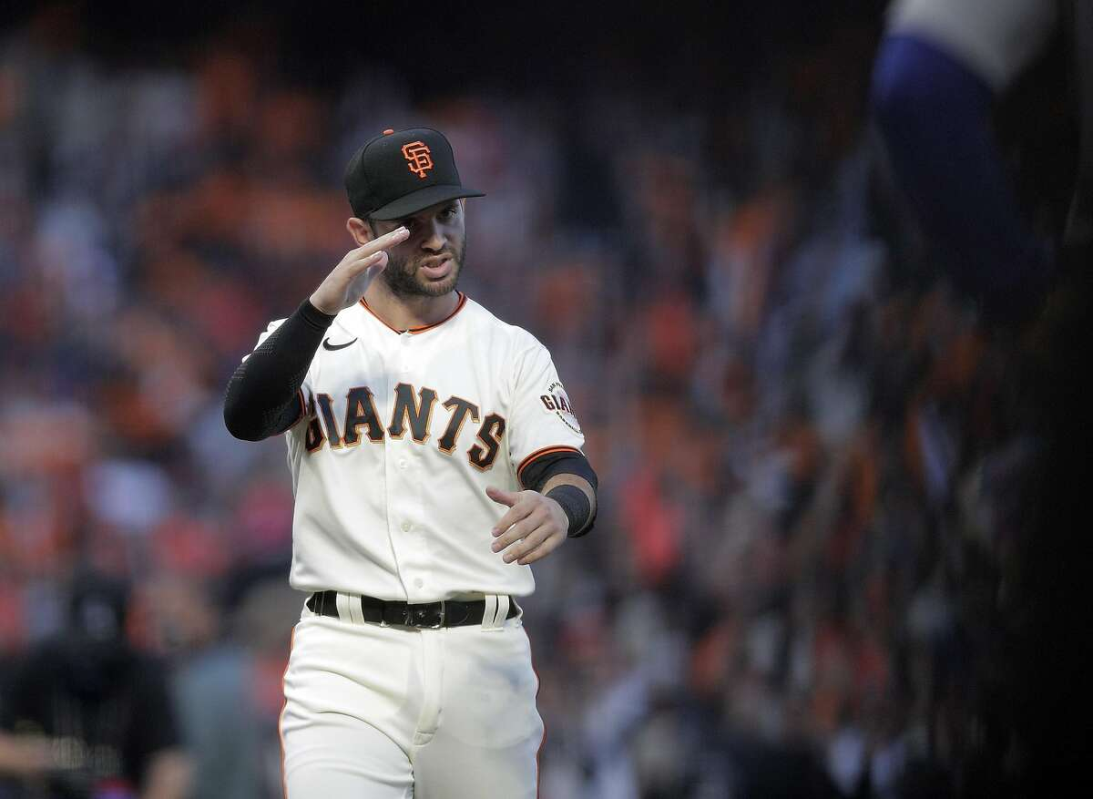 Tommy La Stella (18) gestures to the Dodgers during pregame ceremonies as the San Francisco Giants played the Los Angeles Dodgers in Game 1 of the National League Division Series at Oracle Park in San Francisco, Calif., on Friday, October 8, 2021.