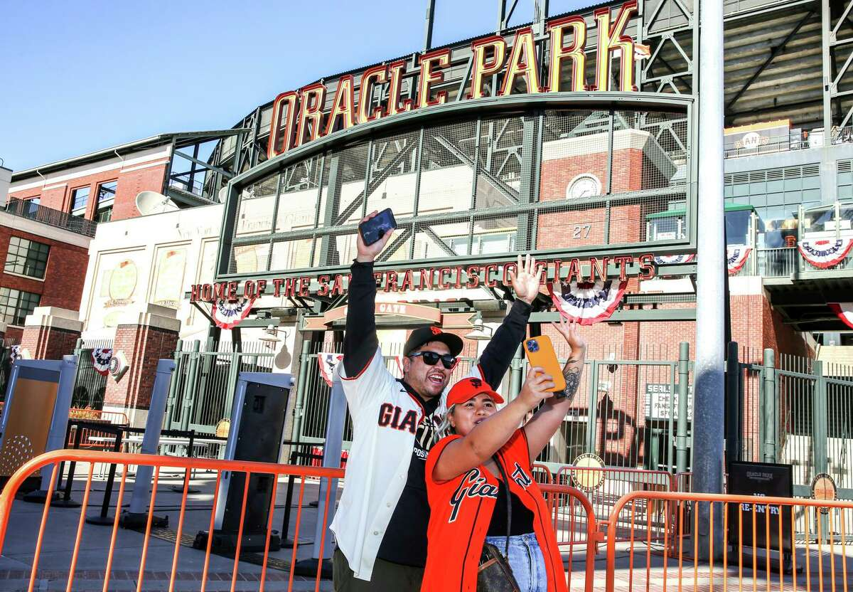 Giants fans Courtney Torres and Sam Alarcon pose for a photo outside the entrance of Oracle Park.