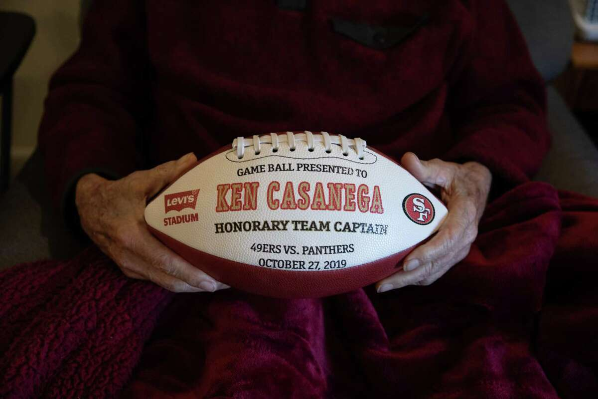 Ken Casanega, 100, the oldest living member of the 49ers, holds a football in his assisted living facility, The Springs at Veranda Park, on March 4th, 2020, in Medford, Oregon.