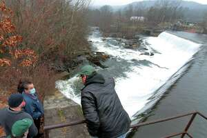 Kevin Zak, head of Naugatuck River Restoration Commission, back to camera, leads a tour of the Kinneytown Dam along the Naugatuck River in Seymour last year.