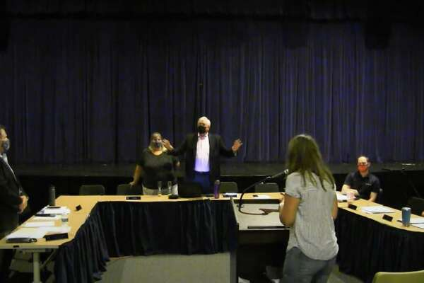 Brookfield's school board meeting was disrupted in mid-September by community members who were against COVID-19 protocols. Bob Belden, vice chairman of the school board member, is pictured in the center with his hands raised as a woman tries to speak at the podium after the meeting had been adjourned.