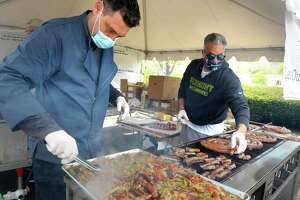 Chef Andrew Testa, left, of Let Out Village Eat (L.O.V.E.), and Johnny Vazzano of Vazzy's Restaurant grill sausage and peppers and other items as they prepare meals for delivery to area hospitals workers, in Bridgeport, Conn. May 7th, 2020, part of the Grubs for Scrubs charity.