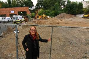 Local artist Kathleen Patricia Thrane, poses near what she claims is a prehistoric indigenous ceremonial art site on a cliff face behind a pending development site along West Main Street in Stamford, Conn., on Wednesday October 13, 2021.