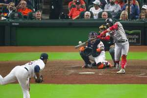 Boston Red Sox center fielder Kike Hernandez (5) hits a game-tying solo home run to start the third inning in Game 1 of the American League Championship Series on Friday, Oct. 15, 2021, at Minute Maid Park in Houston.
